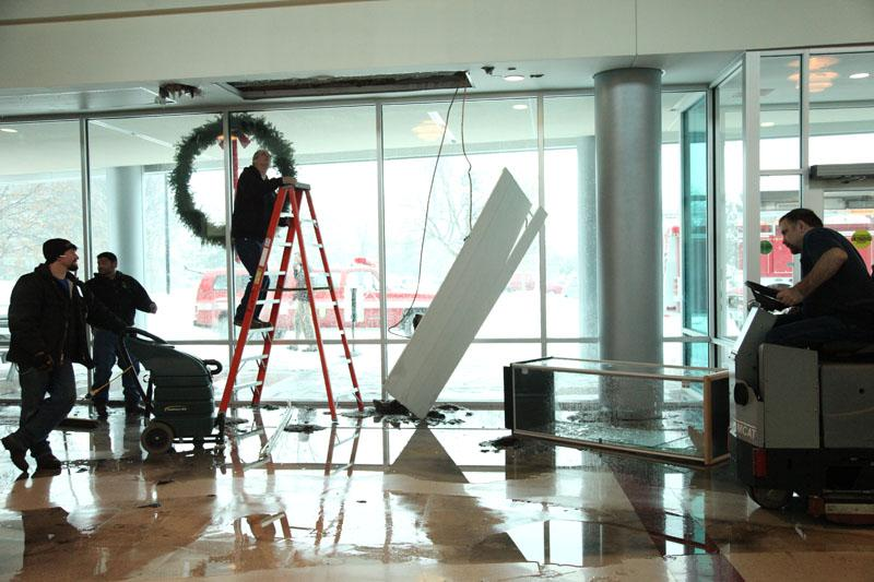 Central janitors respond to the burst pipe at the main entrance of the building caused by the extremely low Naperville temperatures.