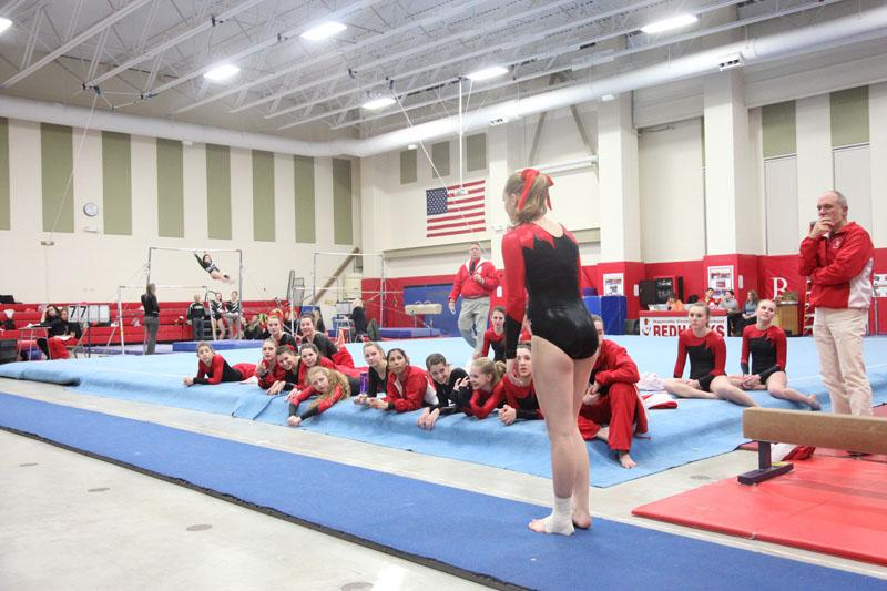 Senior Emily Hufferd anticipates her vault as her teammates watch on.