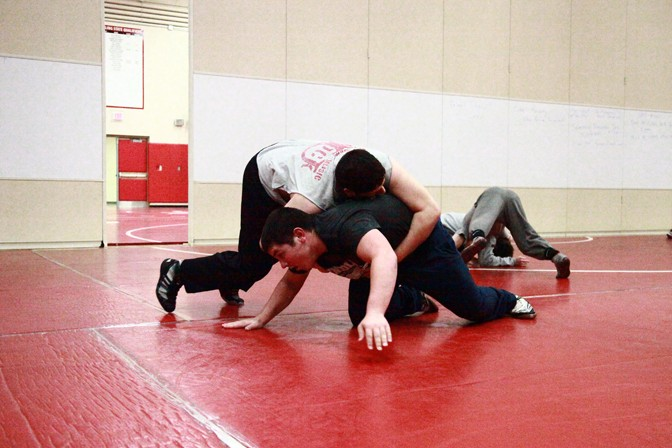 Senior Hayden Saldivar attempts to pin down sophomore Christian Nussbaum during practice.