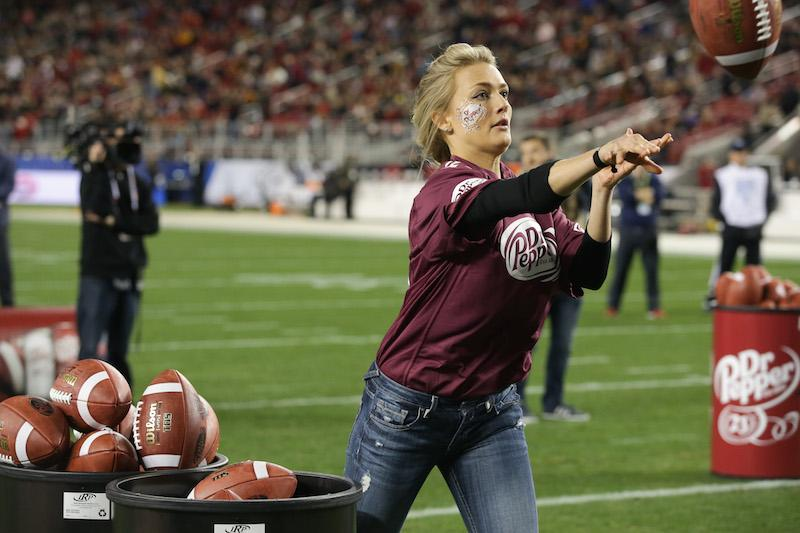 Central alumna Kotryna Staputyte tosses footballs into an oversized Dr. Pepper can to compete for a $100,00 scholarship.