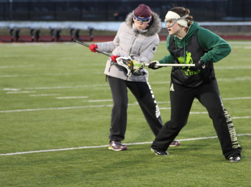 Two girls' lacrosse players fight for the ball in March 2016.