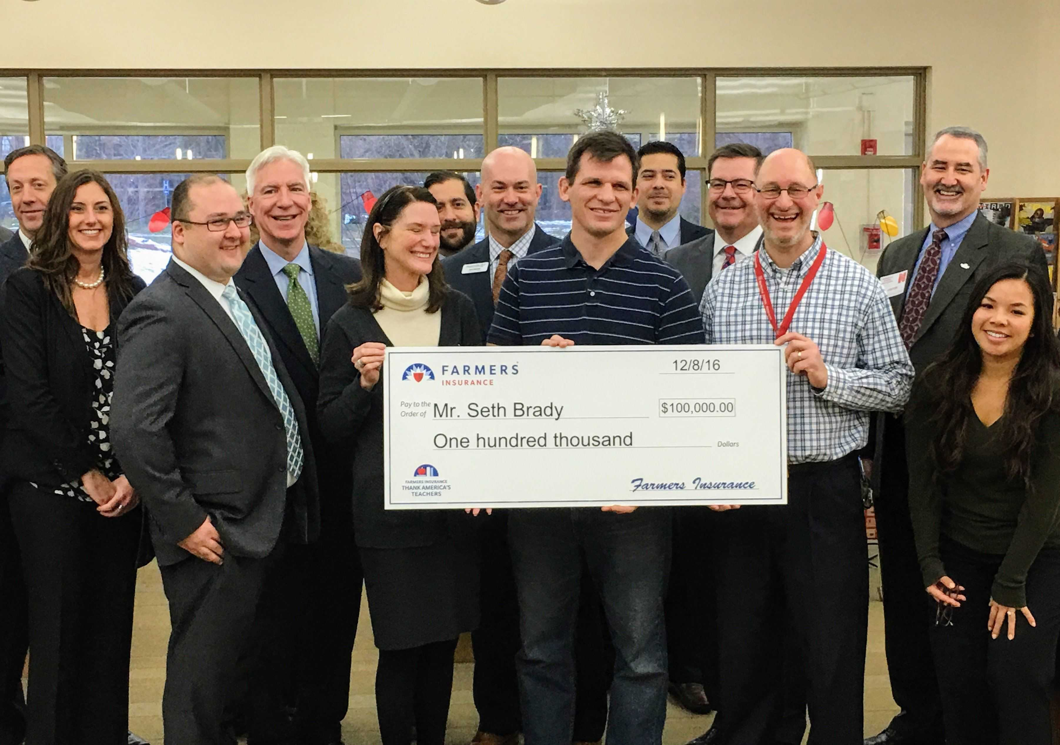 Social studies teachers Seth Brady and Randy Smith hold a check for $100,000 presented by Farmers Insurance. The money will be used to fund Brady's Global Scholar initiative in Illinois. The program has also received state legislative support.
