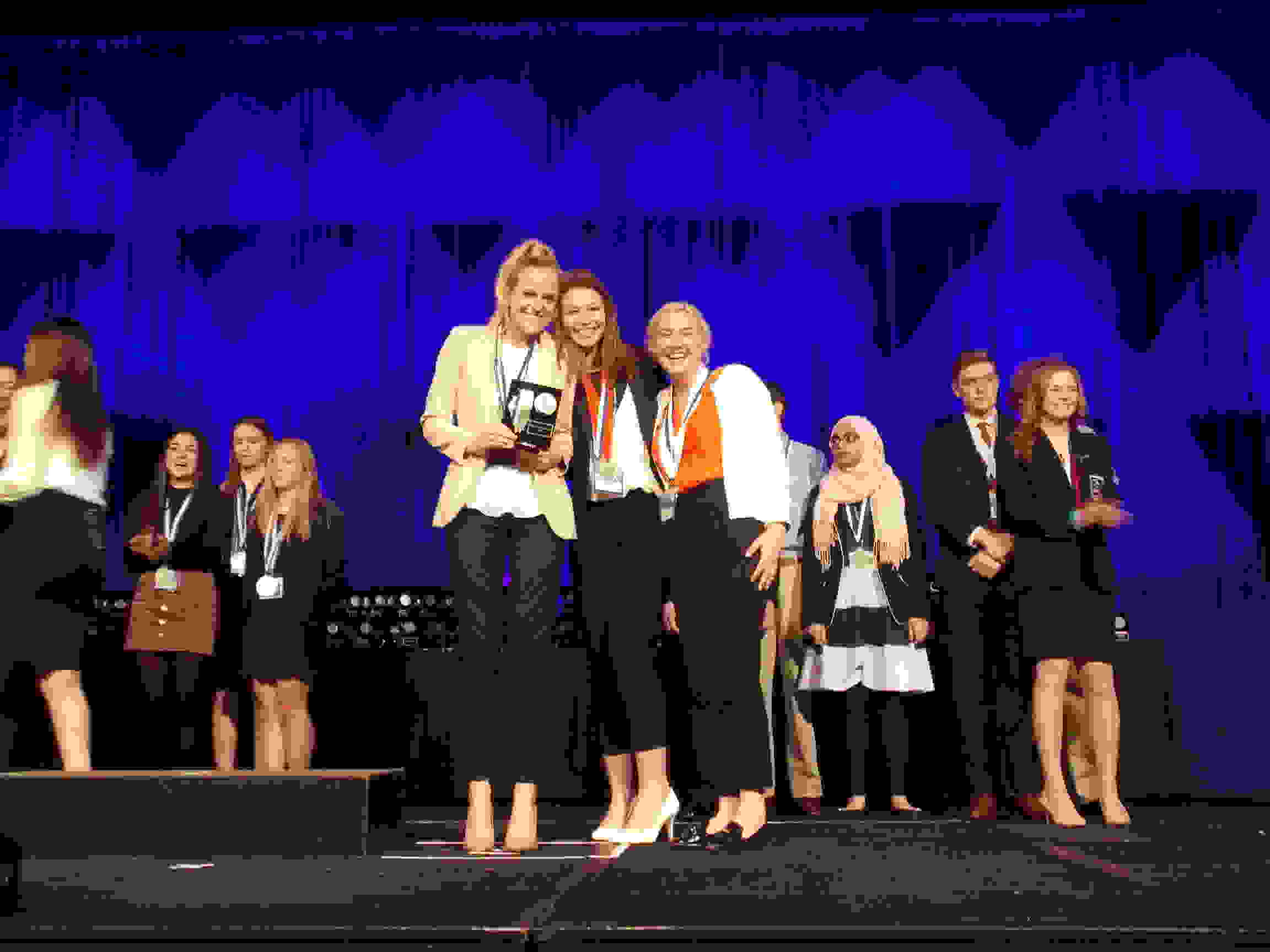 Seniors Mira Piucci, Katie Hunt and Hattie Goodwin pose with their awards at the DECA state competition.