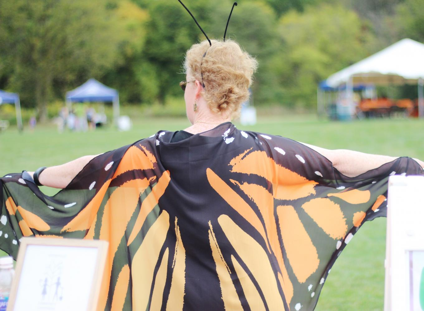 A volunteer greets children and families as they enter the Monarch Festival.