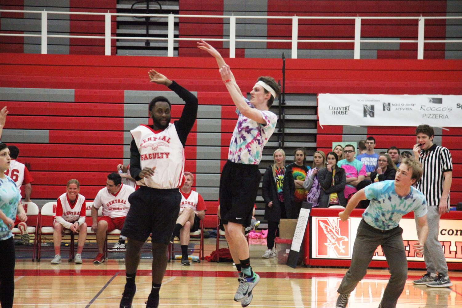 Senior Brian Clune attempts to make a basket during staff versus student basketball game on March 6 at Naperville Central.