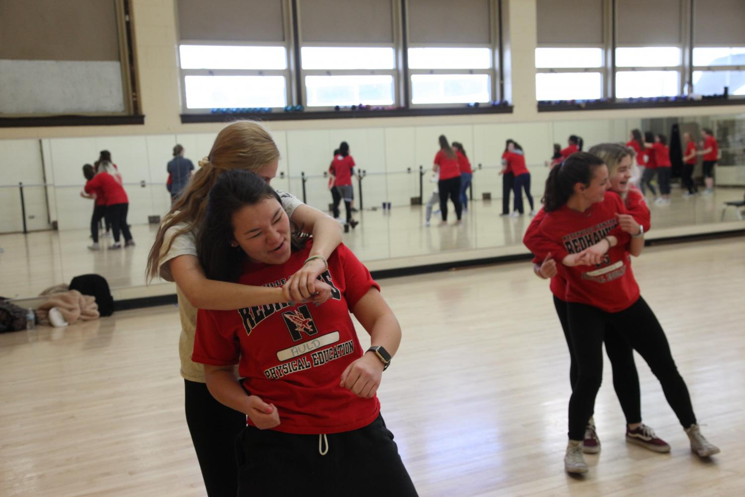 "Seniors Julia Tung and Emilie Mineo defend themselves in a simulated attack. ""I feel much more prepared and confident heading off to college next year,"" Tung said. ""This class has taught me a lot of helpful self-defense techniques."""