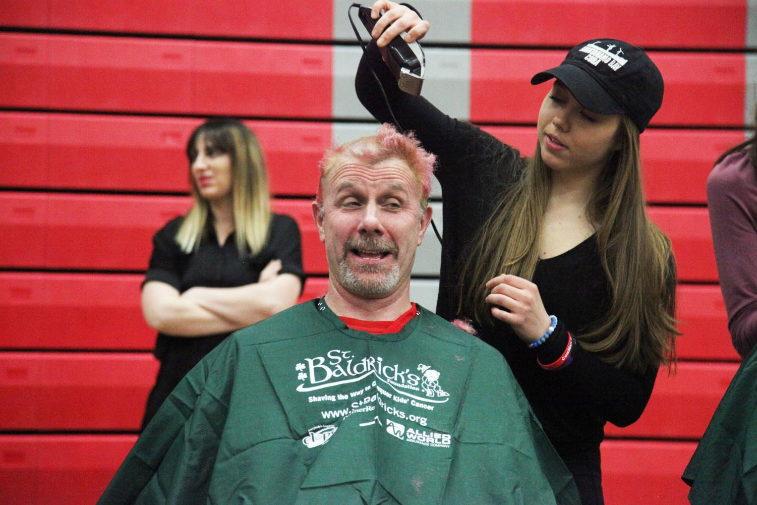 Senior Mary Amato shaves social studies teacher Todd Holmberg's head. Each year, he asks his classes to raise money for St. Baldrick's. Students bring in money to enter a raffle for the chance to shave his head.