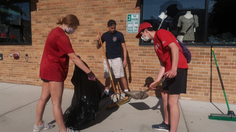 Naperville teens work together to sweep up broken glass caused by Monday night vandals.