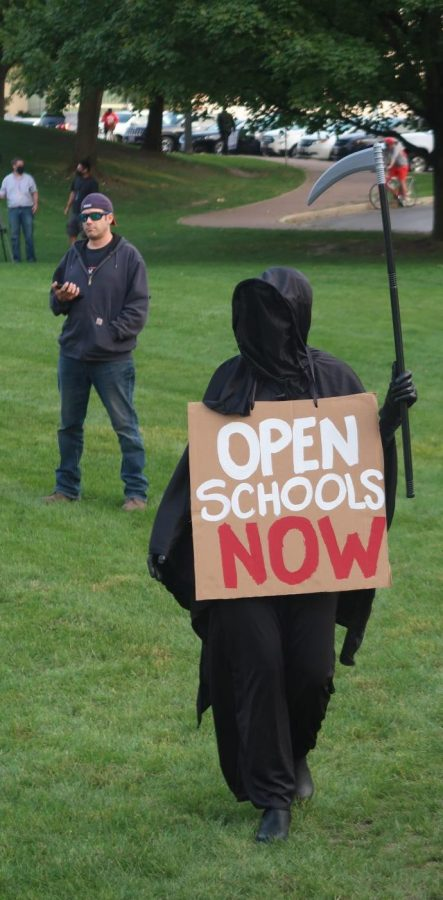 Not everyone in attendance at Mondays rally was in favor of reopening schools. One parent warned of reopening by appearing in costume dressed as the Grim Reaper.
