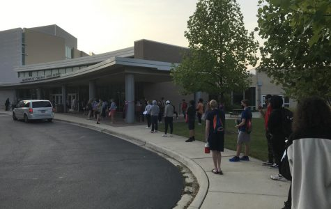 Socially distanced seniors wait in line to enter the school and make up their spring SAT on Sept. 23.