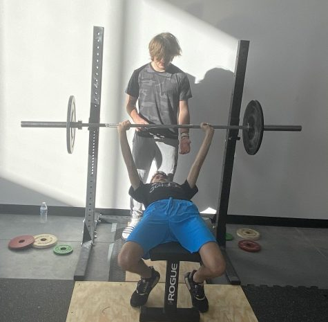 Naperville Central freshman Maverick Ohle (standing) coaches fellow Central freshman Tarek Hassabo on performing a bench press at The PowerHouse, Ohle's Olympic gym located at 505 S Weber St.