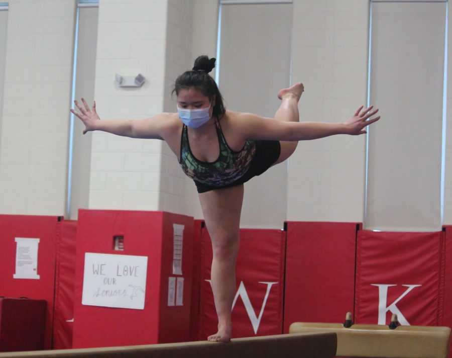 Junior varsity gymnast Anna Chi works on her form in preparation for her balance beam routine during practice at Naperville Central High School on Feb. 12.