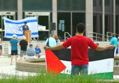 """A Palestinian counter protester silently holds a Palestinian flag at the """"Walk for Israel"""" rally on May 23 at Naperville City Hall."""