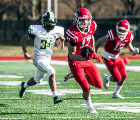 Junior wide receiver Luke Roy shakes off the defense in a game against DVC rival Waubonsie Valley on March 20.