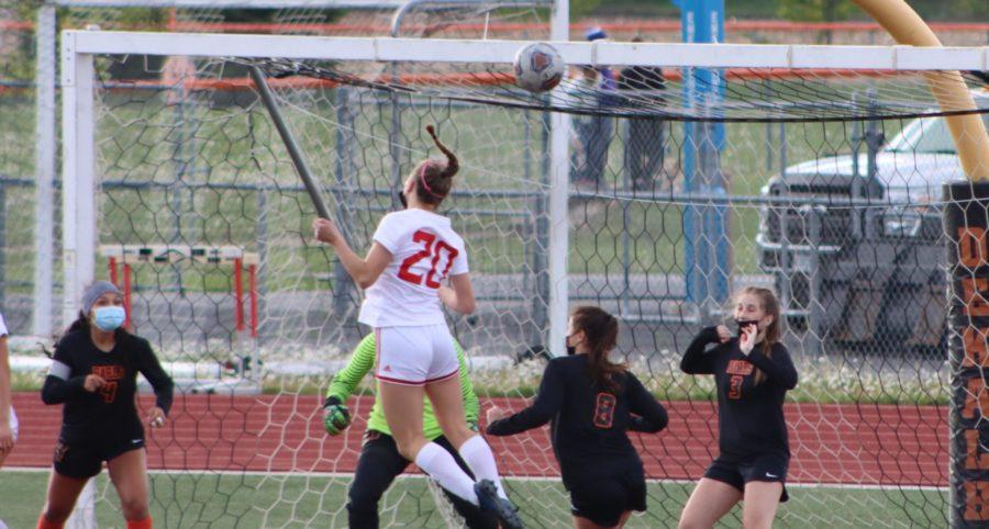 Sophomore varsity center back Ella Burke buries a header into the goal off of a corner kick from junior varsity outside back Sam Sharp against DeKalb High School on May 4.