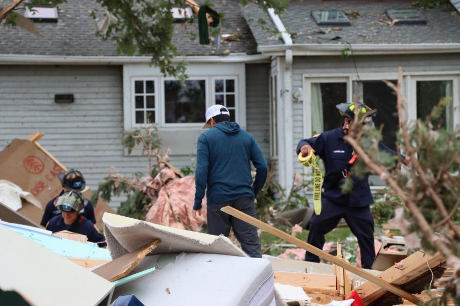 Firefighters help a resident scour for personal items in the debris caused by a tornado that touched down in Naperville on the night of June 20.