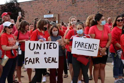 Educators, parents and students rally outside of the Washington Junior High School main entrance in support of the Naperville Unit Education Association