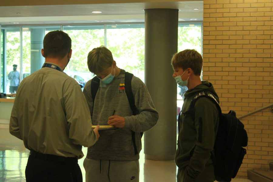 Dean Pete Flaherty signs out students rushing out of  Naperville Central in the wake of a threat message circulating the school on Monday, Oct. 18.